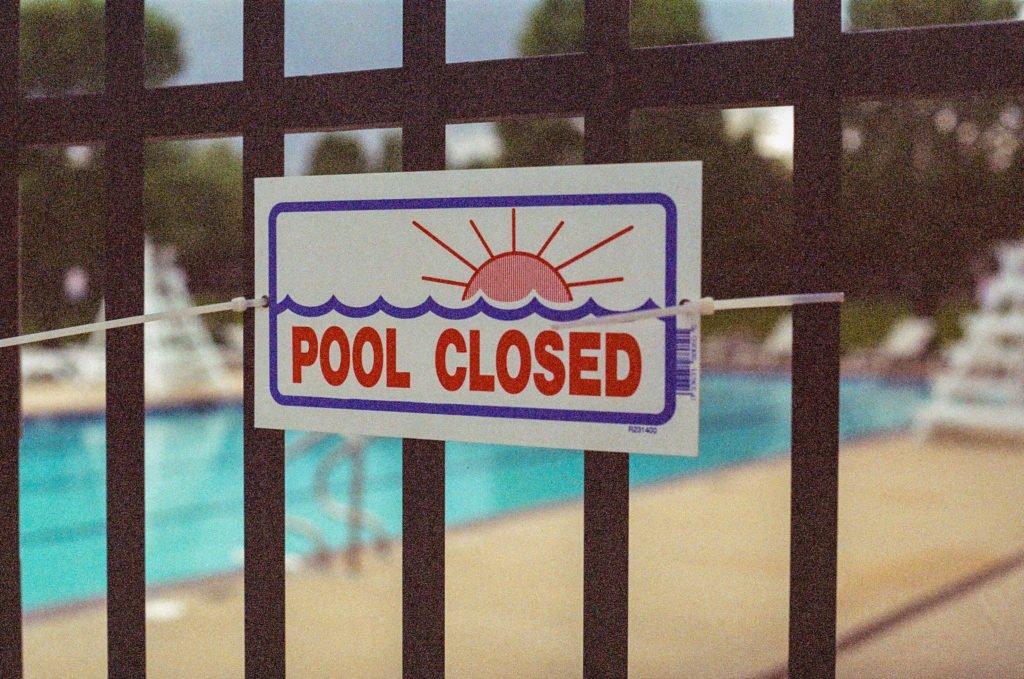 "Fence with 'Pool Closed"" sign on it and a swimming pool in the background"